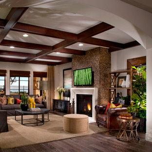 Immagine di un ampio soggiorno boho chic aperto con pareti bianche, parquet scuro, camino classico, cornice del camino in legno e TV a parete