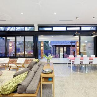 メルボルンの広いコンテンポラリースタイルのおしゃれなオープンリビング (白い壁、コンクリートの床、標準型暖炉、レンガの暖炉まわり、壁掛け型テレビ) の写真