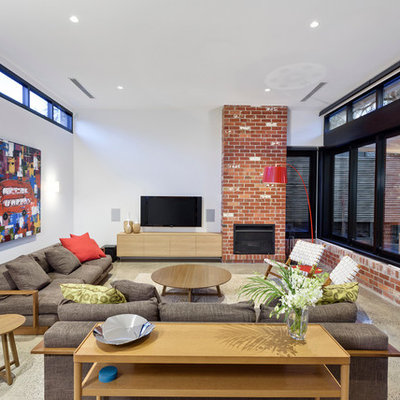 Example of a trendy family room design in Melbourne with white walls, a standard fireplace and a wall-mounted tv