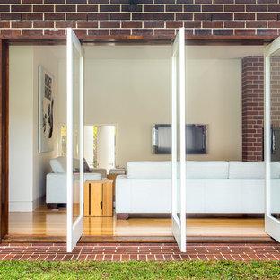 Diseño de sala de estar abierta, contemporánea, con paredes beige, suelo de madera en tonos medios, televisor colgado en la pared y marco de chimenea de ladrillo