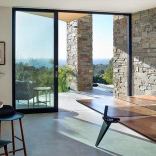 Cette image montre une grand salle de séjour minimaliste fermée avec salle de jeu, un mur blanc, béton au sol et un sol gris.