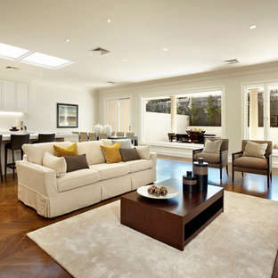 Family room - large traditional open concept medium tone wood floor family room idea in Melbourne with white walls
