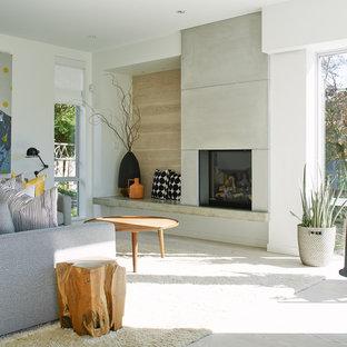 バンクーバーの中くらいのコンテンポラリースタイルのおしゃれなオープンリビング (白い壁、淡色無垢フローリング、標準型暖炉、コンクリートの暖炉まわり) の写真
