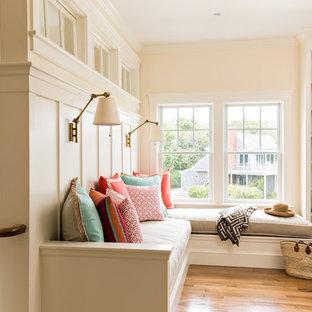 Réalisation d'une petite salle de séjour mansardée ou avec mezzanine tradition avec un mur beige, un sol en bois brun, aucune cheminée, aucun téléviseur et un sol marron.