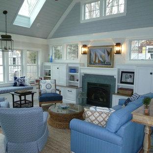 Idée de décoration pour une grande salle de séjour marine ouverte avec un mur bleu, un sol en brique, une cheminée standard et un manteau de cheminée en pierre.