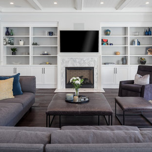 Example of a coastal dark wood floor and brown floor family room design in Los Angeles with white walls, a standard fireplace, a stone fireplace and a wall-mounted tv