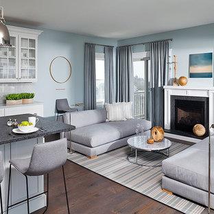 ニューヨークの大きいビーチスタイルのおしゃれなファミリールーム (青い壁、濃色無垢フローリング、標準型暖炉、木材の暖炉まわり、茶色い床) の写真