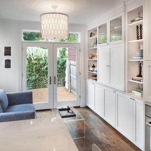 Diseño de sala de estar abierta, actual, pequeña, sin chimenea, con paredes blancas, suelo de madera en tonos medios y televisor retractable