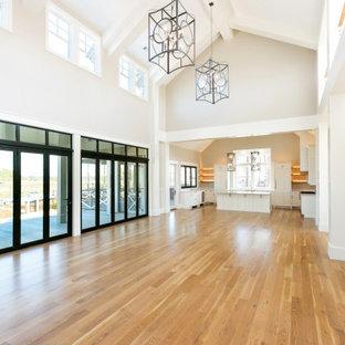 チャールストンの巨大なビーチスタイルのおしゃれなオープンリビング (ベージュの壁、無垢フローリング、標準型暖炉、石材の暖炉まわり、壁掛け型テレビ、茶色い床、表し梁、塗装板張りの壁) の写真