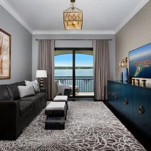 Modelo de sala de estar marinera, grande, sin chimenea, con paredes grises, suelo de madera oscura y televisor colgado en la pared