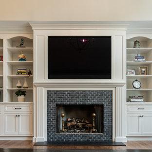 Inspiration pour une grand salle de séjour traditionnelle ouverte avec un mur beige, un sol en bois brun, une cheminée standard, un manteau de cheminée en brique, un téléviseur fixé au mur et un sol marron.