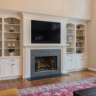 Cette photo montre une grand salle de séjour chic ouverte avec un mur beige, un sol en bois brun, une cheminée standard, un manteau de cheminée en brique, un téléviseur fixé au mur et un sol marron.