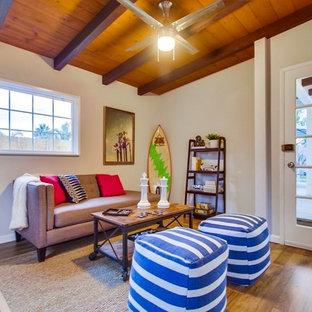 サンディエゴの広いビーチスタイルのおしゃれなオープンリビング (ゲームルーム、白い壁、無垢フローリング、コーナー設置型暖炉、レンガの暖炉まわり、据え置き型テレビ、茶色い床) の写真