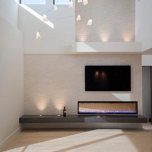 Idee per un grande soggiorno moderno aperto con pareti bianche, parquet chiaro, camino sospeso, cornice del camino piastrellata e TV a parete