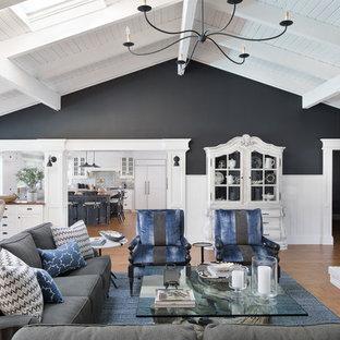 マイアミの大きいビーチスタイルのおしゃれなファミリールーム (黒い壁、無垢フローリング、標準型暖炉、レンガの暖炉まわり、壁掛け型テレビ、茶色い床) の写真
