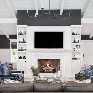 マイアミの広いビーチスタイルのおしゃれなオープンリビング (黒い壁、無垢フローリング、標準型暖炉、レンガの暖炉まわり、壁掛け型テレビ、茶色い床) の写真