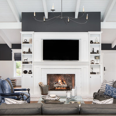 Large beach style open concept medium tone wood floor and brown floor family room photo in Miami with black walls, a standard fireplace, a brick fireplace and a wall-mounted tv