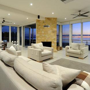 アデレードの巨大なビーチスタイルのおしゃれなファミリールーム (白い壁、セラミックタイルの床、コーナー設置型暖炉、石材の暖炉まわり) の写真