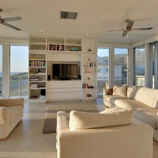 アデレードの巨大なビーチスタイルのおしゃれなオープンリビング (白い壁、セラミックタイルの床、コーナー設置型暖炉、石材の暖炉まわり、据え置き型テレビ) の写真