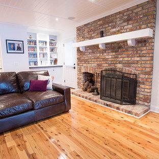 他の地域の中サイズのビーチスタイルのおしゃれなファミリールーム (白い壁、無垢フローリング、標準型暖炉、レンガの暖炉まわり、壁掛け型テレビ) の写真