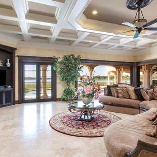 Huge tuscan open concept travertine floor family room photo in Orlando with beige walls and a media wall