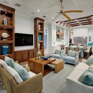 Inspiration pour une salle de séjour marine ouverte et de taille moyenne avec un mur bleu, un sol en bois brun, aucune cheminée, un téléviseur fixé au mur et un sol marron.