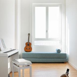 Immagine di un soggiorno moderno chiuso con sala della musica, pareti bianche e pavimento in legno massello medio