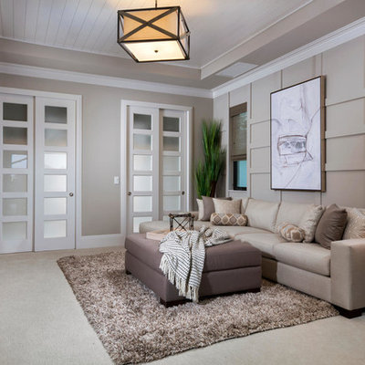 Example of a mid-sized transitional enclosed carpeted and beige floor family room design in Other with no fireplace, a wall-mounted tv and gray walls
