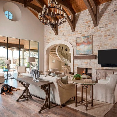 Family room - huge mediterranean open concept light wood floor family room idea in Dallas with white walls, a standard fireplace, a stone fireplace and a wall-mounted tv