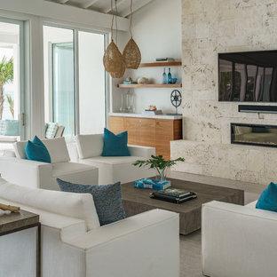 マイアミの広いビーチスタイルのおしゃれなファミリールーム (白い壁、コンクリートの床、石材の暖炉まわり、壁掛け型テレビ、グレーの床、横長型暖炉) の写真
