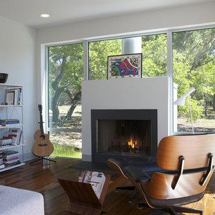 Imagen de sala de estar minimalista con paredes blancas, suelo de madera oscura, chimenea tradicional y suelo marrón