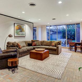 Cette photo montre une grande salle de séjour rétro ouverte avec salle de jeu, un mur blanc, un sol en brique, aucune cheminée et un téléviseur fixé au mur.