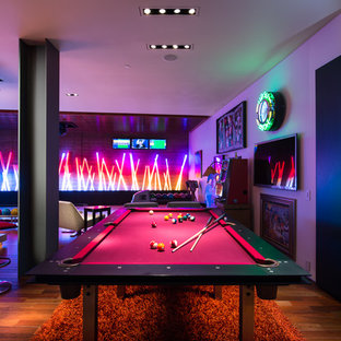 Example of a trendy medium tone wood floor game room design in Las Vegas with a wall-mounted tv