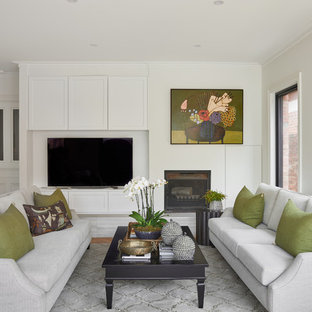 Photo of a transitional family room in Melbourne with white walls, medium hardwood floors, a standard fireplace, a freestanding tv and brown floor.