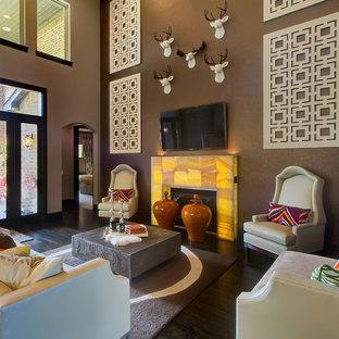 Foto de sala de estar ecléctica con paredes marrones, suelo de madera oscura, chimenea tradicional y televisor colgado en la pared