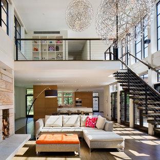 ニューヨークの大きいコンテンポラリースタイルのおしゃれなファミリールーム (白い壁、無垢フローリング、標準型暖炉、石材の暖炉まわり、据え置き型テレビ) の写真