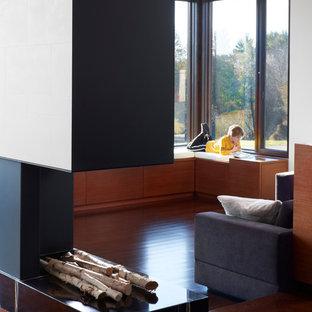 Immagine di un soggiorno minimal aperto con pareti bianche, parquet scuro, camino bifacciale, cornice del camino in pietra e pavimento marrone