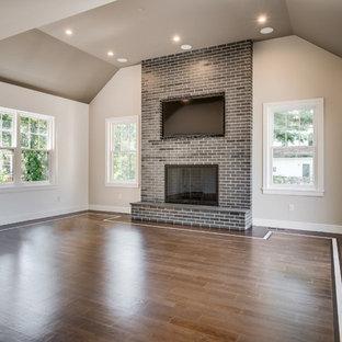フィラデルフィアの広いコンテンポラリースタイルのおしゃれな独立型ファミリールーム (ベージュの壁、濃色無垢フローリング、標準型暖炉、レンガの暖炉まわり、埋込式メディアウォール、茶色い床) の写真