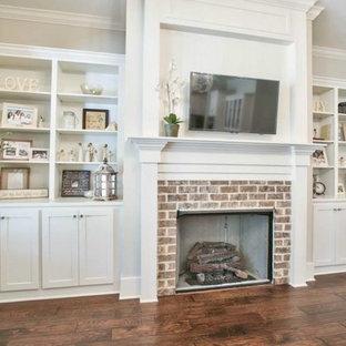 アトランタの大きいビーチスタイルのおしゃれなファミリールーム (白い壁、無垢フローリング、標準型暖炉、レンガの暖炉まわり、壁掛け型テレビ) の写真