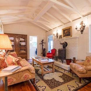 Imagen de sala de estar cerrada, de estilo de casa de campo, pequeña, con paredes blancas, suelo de madera en tonos medios y chimenea tradicional