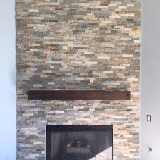 フェニックスのトラディショナルスタイルのおしゃれなファミリールーム (グレーの壁、磁器タイルの床、コーナー設置型暖炉、石材の暖炉まわり、茶色い床) の写真