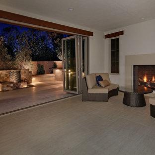 オレンジカウンティの中くらいのコンテンポラリースタイルのおしゃれなオープンリビング (ゲームルーム、白い壁、ライムストーンの床、標準型暖炉、コンクリートの暖炉まわり、テレビなし) の写真