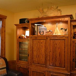 デンバーの中サイズのサンタフェスタイルのおしゃれな独立型ファミリールーム (黄色い壁、ラミネートの床、薪ストーブ、漆喰の暖炉まわり、据え置き型テレビ) の写真
