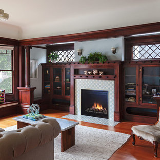 Elegant medium tone wood floor family room library photo in San Francisco with blue walls, a standard fireplace and a tile fireplace