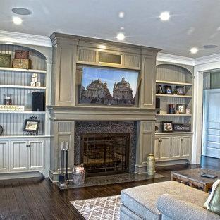 Immagine di un soggiorno chic di medie dimensioni e aperto con pareti verdi, parquet scuro, camino classico, cornice del camino in pietra e TV a parete