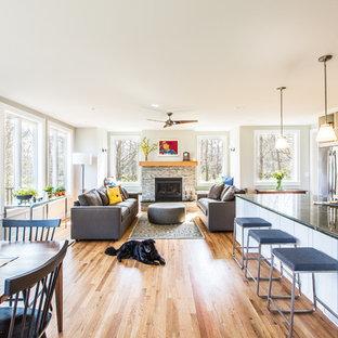 Exemple d'une grande salle de séjour craftsman ouverte avec un mur beige, un sol en bois clair, une cheminée standard, un manteau de cheminée en pierre et aucun téléviseur.