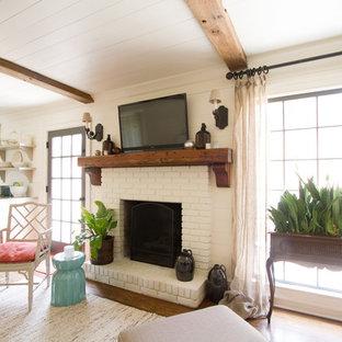 Imagen de sala de estar abierta, clásica, con paredes beige, suelo de madera en tonos medios, chimenea tradicional, marco de chimenea de ladrillo y televisor colgado en la pared