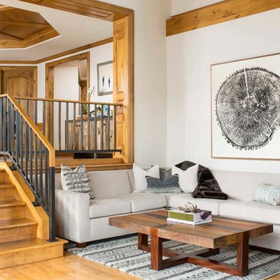 Huge mountain style medium tone wood floor family room photo in Denver with white walls and a wall-mounted tv