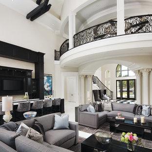Cette image montre une salle de séjour traditionnelle ouverte avec un bar de salon, un mur beige, un téléviseur fixé au mur et un sol blanc.