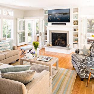 Modelo de sala de estar costera con paredes beige, suelo de madera clara, chimenea tradicional, televisor colgado en la pared y suelo beige
